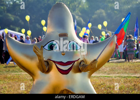 Depicts a man in a funny costume in the form of a star with a flag in his hand at the festival. - Stockfoto