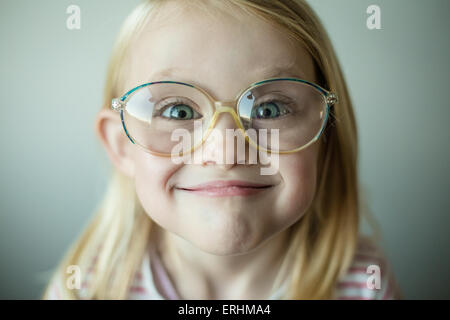 Girl wearing glasses making a silly face - Stock Photo