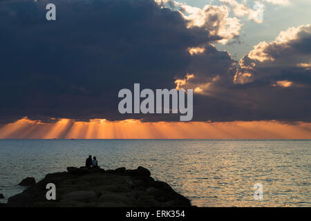 Dramatic sky with orange sun rays reaching down to the water on the horizon out of storm clouds; Paphos, Cyprus - Stock Photo