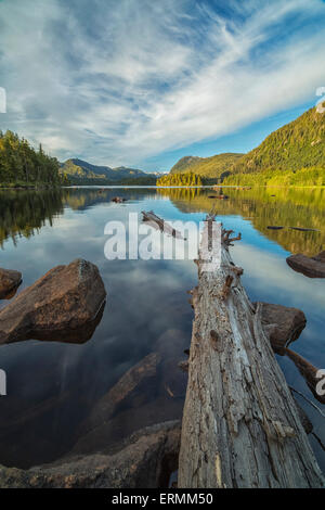 Late afternoon sun lights up a small lake with clouds reflected in the water; Prince Rupert, British Columbia, Canada - Stock Photo