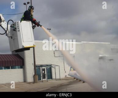 worker de-icing commercial airliner wing Cincinnati Ohio - Stock Photo