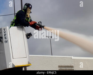 worker de-icing commercial airliner wing Cincinnati Ohio - Stock Photo