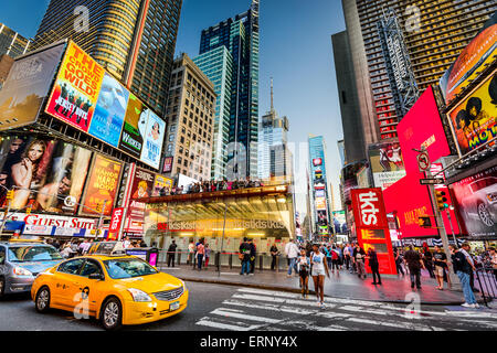 Times Square crowds and traffic at dusk in New York City. - Stock Photo