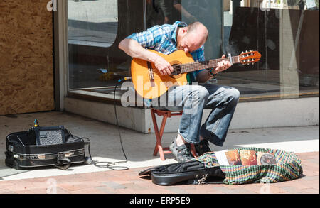 Busker playing a guitar in a town centre , UK on a sunny day - Stock Photo