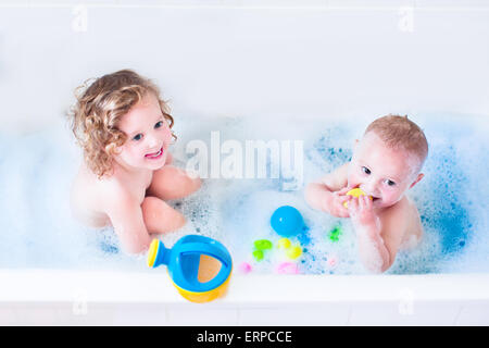 Funny little girl and her cute baby brother having fun taking bath playing in water with foam with colorful toys - Stock Photo