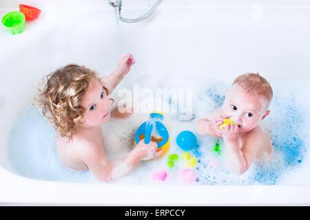 Lustige kleine Mädchen und ihr süßes Baby Bruder Spaß unter Bad spielen im Wasser mit Schaum mit bunten Spielzeug - Stockfoto