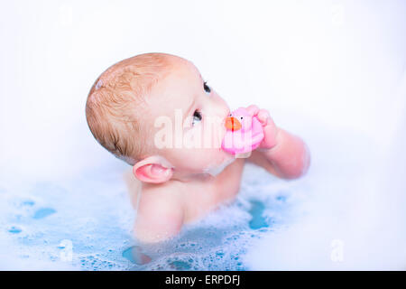 Cute baby boy taking a bubble bath with foam playing in water with a rubber duck toy after shower - Stock Photo