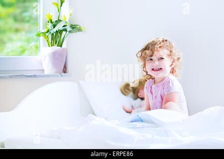 Funny curly toddler girl waking up on a early sunny morning in a white bedroom with window playing with her toys - Stockfoto