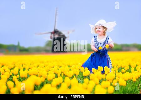 Toddler girl wearing Dutch traditional national costume dress and hat playing in a field of blooming tulips next - Stock Photo