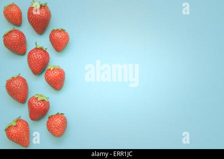 Composition of strawberries on a blue background. - Stock Photo