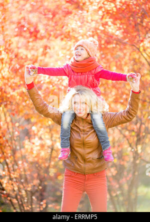 Happy parent and kid walking in fall outdoor - Stock Photo