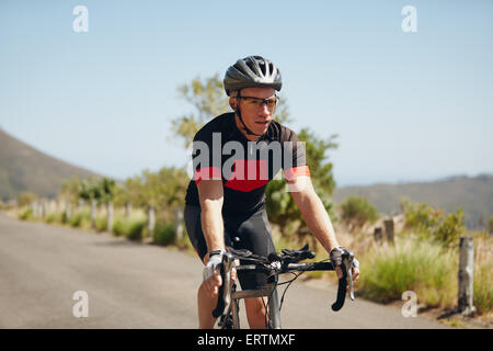 Man triathlon athlete cyclist riding down hill on country road. Young man riding bicycle on open road, practicing - Stockfoto