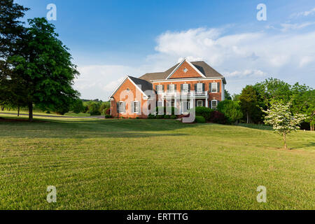 Front garden of a large detached house with red gravel for American family homes