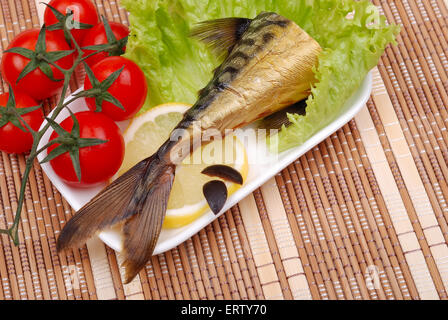 Composition from a smoked mackerel on a plate with vegetables - Stock Photo