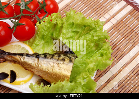 Smoked mackerel on a plate with vegetables - Stock Photo