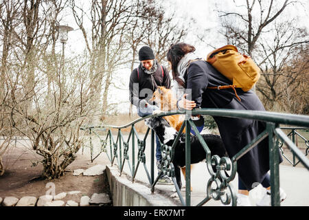 Couple with dogs standing on bridge at park - Stock Photo