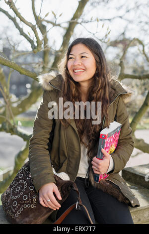 Teenage girl with book and bag sitting on retaining wall ...