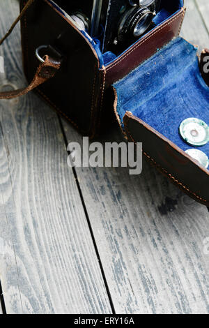 Old retro camera and belt bag (leather case) on vintage wooden boards (desk, table), abstract background - Stock Photo