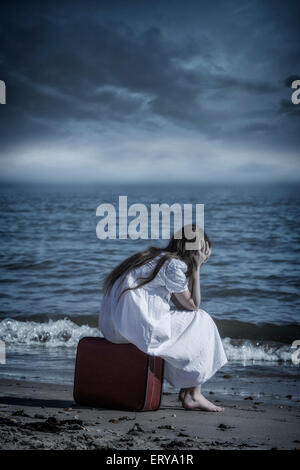 a girl is sitting on a red suitcase at the sea - Stock Photo