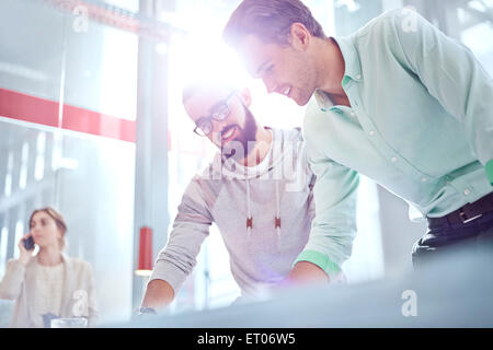 Businessmen working in sunny office - Stock Photo