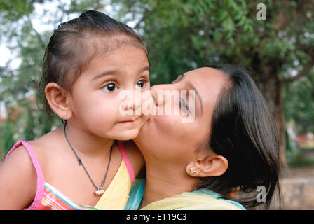 Mother kissing on cheek of daughter MR#736K;736L - Stock Photo