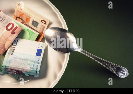 Various euro banknotes in white plate with spoon on one side, conceptual composition about money. - Stock Photo