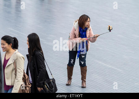 Young girl taking a selfie by using a selfie stick near Tower of London - Stock Photo