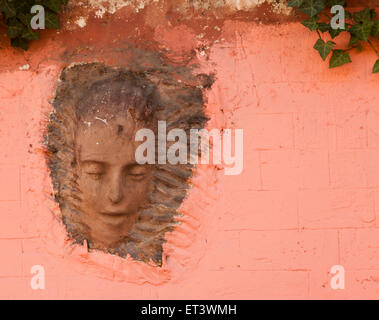 A relief of a head on the wall of the Lapin Agile, a cabaret club in Montmartre, Paris France - Stock Photo