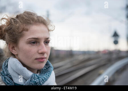 Close-up of young woman thinking with railway tracks in the background Munich Bavaria Germany - Stock Photo