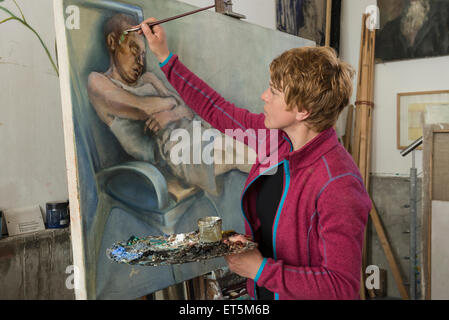 Woman painting at easel, Bavaria, Germany - Stock Photo