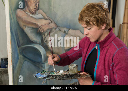 Woman mixing colors while painting, Bavaria, Germany - Stock Photo