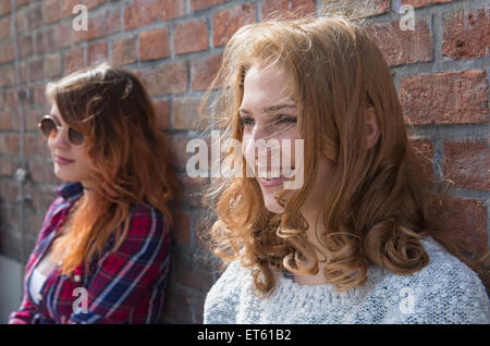 Two women leaning in front of brick wall, Munich, Bavaria, Germany - Stock Photo