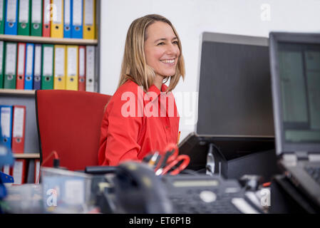 Woman working in office and smiling, Munich, Bavaria, Germany - Stock Photo