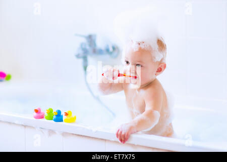 Cute little baby boy brushing his teeth, taking bath playing with foam and colorful rubber duck toys in a white - Stock Photo