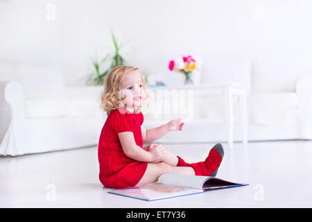 Cute little girl with curly hair wearing a warm knitted red dress and socks reading a book sitting on the floor - Stock Photo