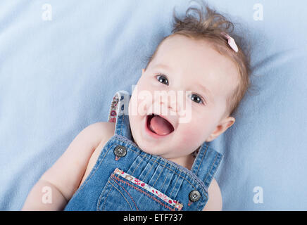 Sweetest baby girl playing with a colorful mobile toy - Stock Photo