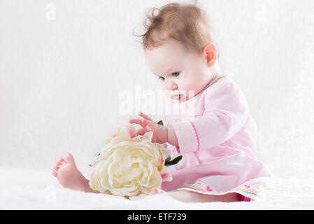 Sweetest little baby girl playing with a huge white flower - Stock Photo