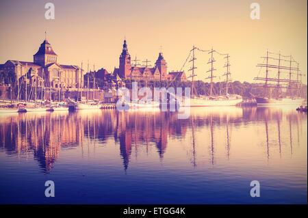 Vintage retro toned photo of sailing ships by Chrobry Embankment at sunrise in Szczecin, Poland. - Stock Photo