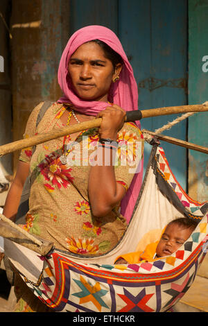 Rajasthani woman carrying her baby in a sling. Jaisalmer, Rajasthan, India - Stock Photo