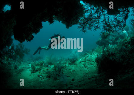 A diver explores the mouth of a deep cave in Raja Ampat, Indonesia. - Stock Photo