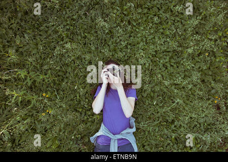woman lying in grass photographing sky - Stock Photo