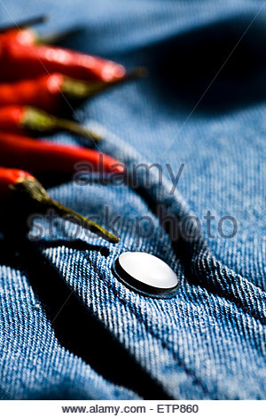 Close-up of red chilli peppers on denim shirt. - Stock Photo