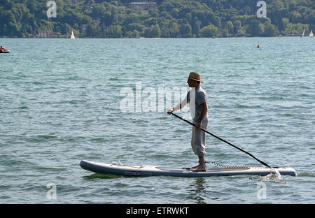 Stand up paddle surfing or standing paddle boarding on Lake Annecy in France - Stock Photo