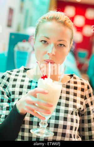 Woman drinking milk shake in diner. - Stock Photo