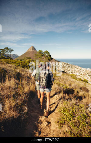 Rear view of couple walking through country path on mountain. Young man and woman hiker hiking in nature. Trekking - Stock Photo