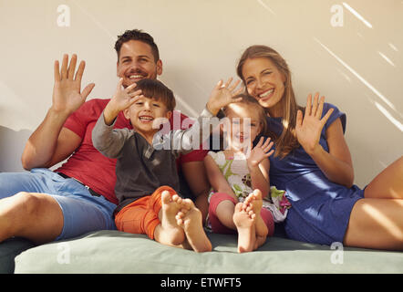 Family sitting on couch smiling and laughing together, waving at camera. Couple with kids on patio having fun outdoors - Stock Photo