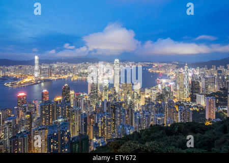 Night skyline of Hong Kong and Victoria Harbour from The Peak on a clear day - Stock Photo
