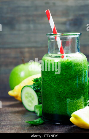 Fresh organic green smoothie with spinach, cucumber, parsley, celery and lemon on wooden background - Stock Photo