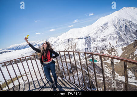 Young woman taking selfie at Soviet-Georgian Friendship monument located on Georgian Military Highway near Guduari - Stock Photo