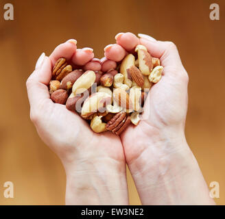 Woman holding a handful of mixed nuts - Stock Photo